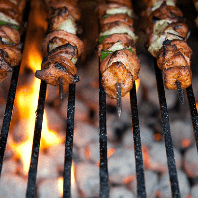 Barbequiing pork and vegeytable kebabs